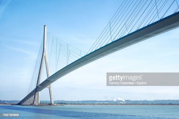suspension bridge over river against sky - suspension bridge stock photos and pictures