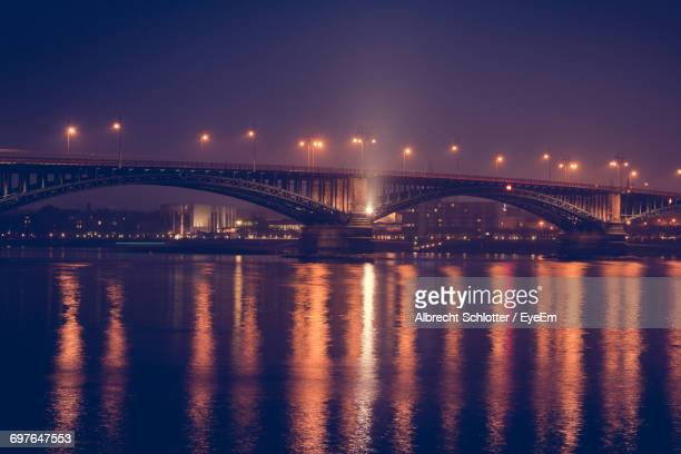 suspension bridge over river at night - albrecht schlotter stock photos and pictures