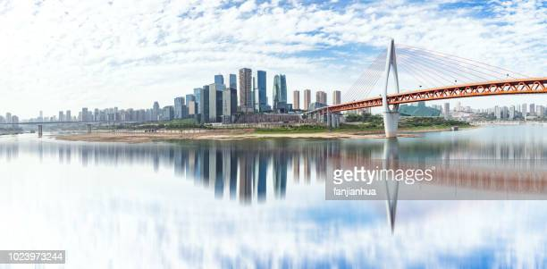 suspension bridge over river in modern city - chongqing stock photos and pictures