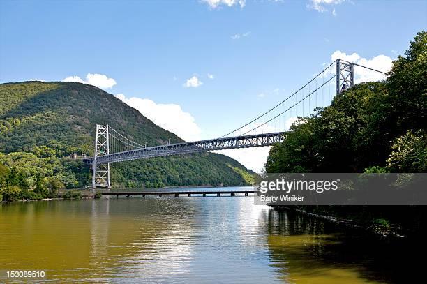 suspension bridge over river near mountain. - bear mountain bridge stock pictures, royalty-free photos & images