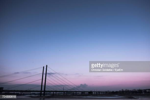 suspension bridge over sea against sky during sunset - christian soldatke stock pictures, royalty-free photos & images