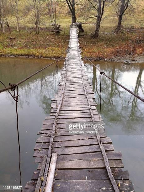 suspension bridge over the river, rural scene in transylvania, romania. - footbridge stock photos and pictures
