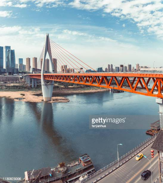 suspension bridge over yangtze river connected with chongqing cityscape - yangtze river stock pictures, royalty-free photos & images