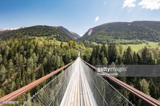 suspension bridge over young rhone river near ernen, valais, switzerland, known as 'goms bridge', 2018 - hängebrücke stock-fotos und bilder