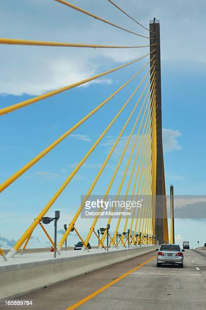 suspension bridge vivid yellow ties on highway against cloudy sky - sunshine skyway bridge stock photos and pictures