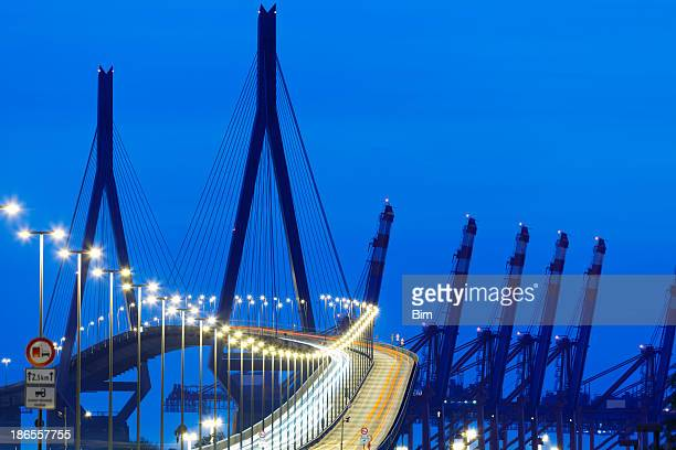 suspension bridge with car light trails at night - köhlbrandbrücke stock photos and pictures
