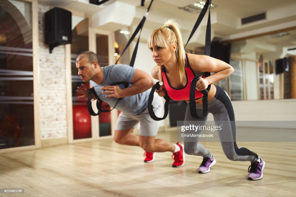 TRX suspension training- couple doing arm exercises : Stock Photo