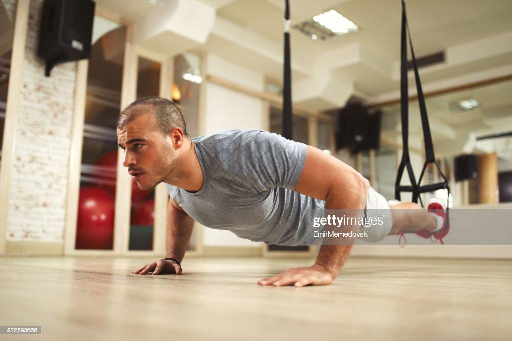 TRX suspension training- man doing push ups : Stock Photo