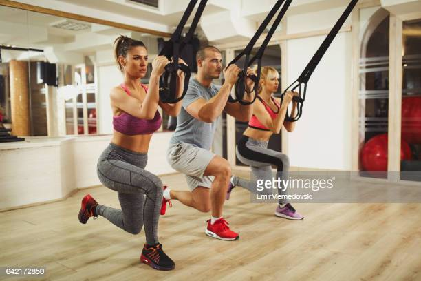 TRX suspension training- people doing arm and leg exercises