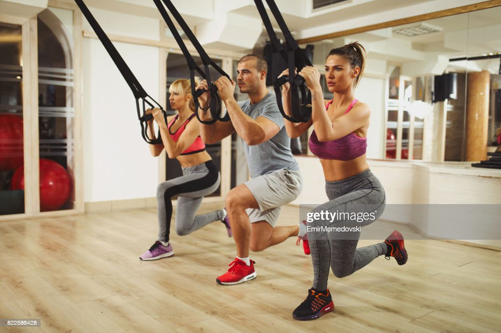 TRX suspension training- people doing arm and leg exercises : Stock Photo
