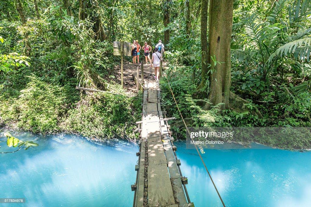 Suspension wooden bridge crossing Rio Celeste river, Costa Rica : Foto de stock