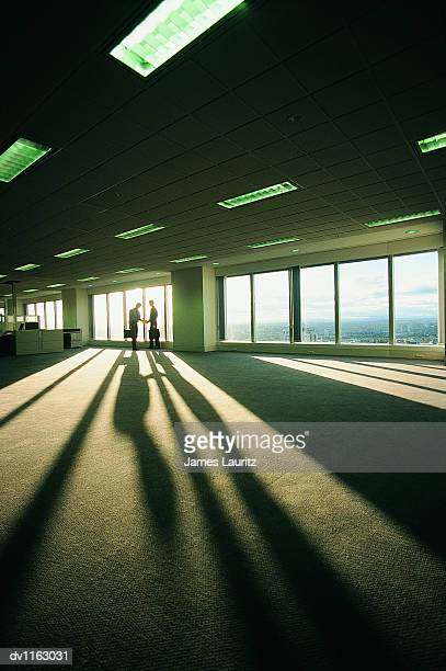 Suspicious Businessman Passing on An Envelope to Another Businessman in An Empty Open Plan Office