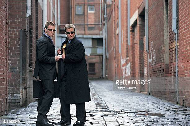 Suspicious Businessmen Standing in a Backstreet Giving and Receiving a Bundle of Money and An Envelope