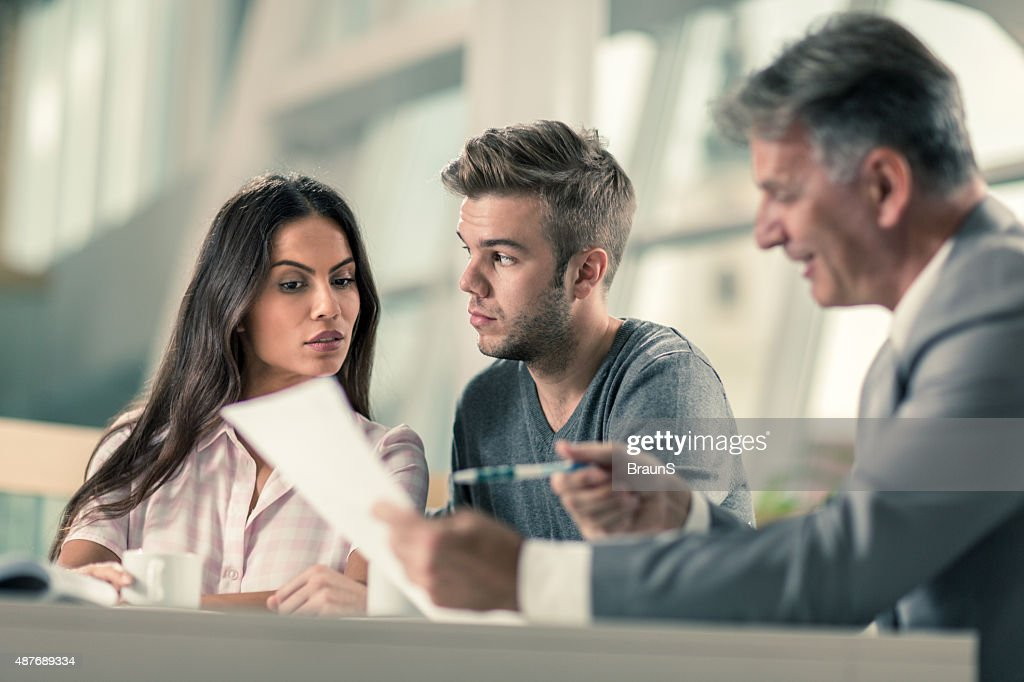 Suspicious couple having a business meeting with real estate agent. : Stock Photo