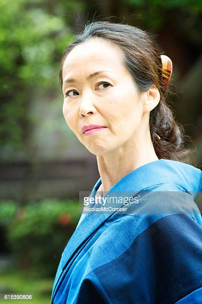 suspicious critical mature japanese woman looking back over her shoulder - 残酷 ストックフォトと画像