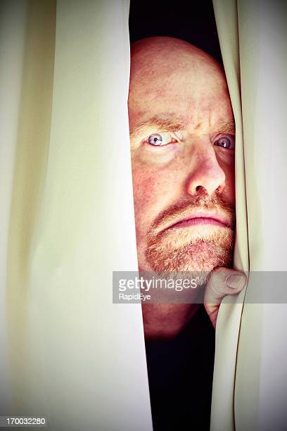 Suspicious, frowning man peers sideways through closed curtains