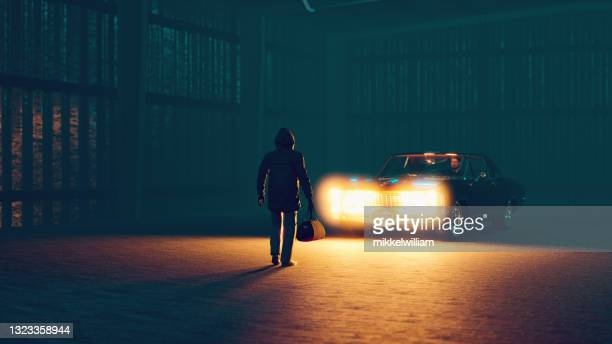 suspicous meeting at night where a bag is exchanged - in silhouette stock pictures, royalty-free photos & images