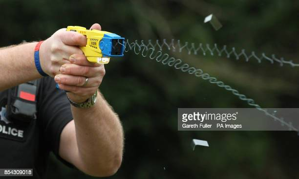 A Sussex police officer demonstrates the use of a Taser during a media conference at police headquarters in Lewes Sussex as around 160 Sussex police...