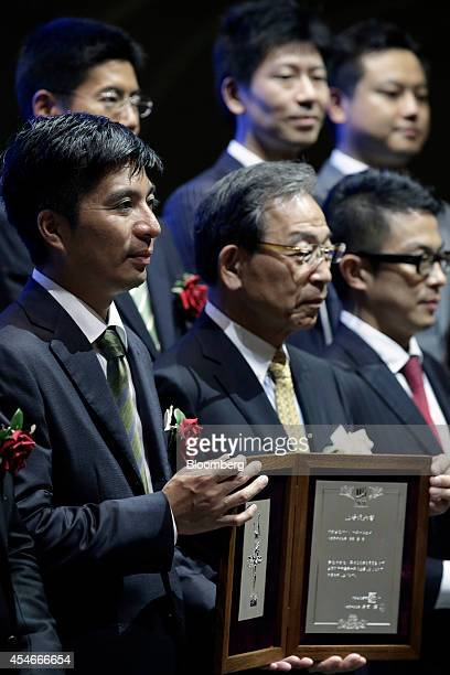 Susumu Fujita president of CyberAgent Inc front row left holds a listing notice with Akira Kiyota president of Tokyo Stock Exchange Inc front row...