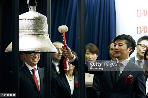 Susumu Fujita president of CyberAgent Inc right hits a bell during an initial public offering ceremony for the company's listing at the Tokyo Stock...