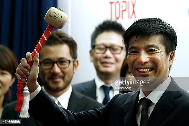 Susumu Fujita president of CyberAgent Inc right poses for photographs before hitting a bell during an initial public offering ceremony for the...