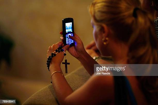 Susy Vazquez uses her camera phone to photograph a shadow that has formed what many think is the silhouette of the Holy Family Joseph and the Virgin...