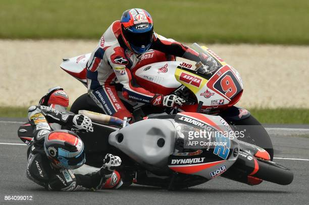 Suter rider Marcel Schrotter of Germany crashes as Federal Oil Gresini Kalex rider Jorge Navarro of Spain looks on during the Moto2class third...