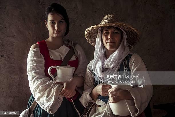 Sutlers holding jugs, 18th century. Historical reenactment.
