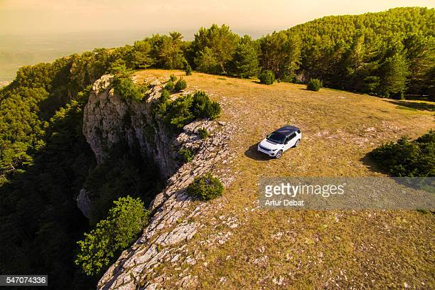 Suv car place on the top of mountain with beautiful view of the Catalan Pyrenees on sunset light during a road trip to discover the hidden places of the region.
