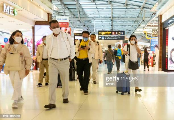 suvarnabhumi airport, bangkok, thailand. people some with face walking. - thailand stock pictures, royalty-free photos & images