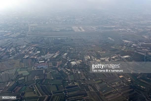 Suvarnabhumi International Airport and rice paddy in Samut Prakan province in Thailand, daytime aerial view from airplane