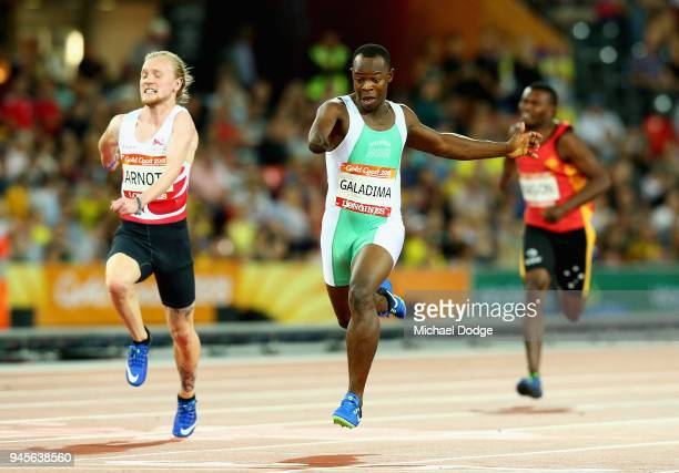 Suwaibidu Galadima of Nigeria crosses the line to win gold ahead of James Arnott of England in the Men's T47 100m Finalduring athletics on day nine...