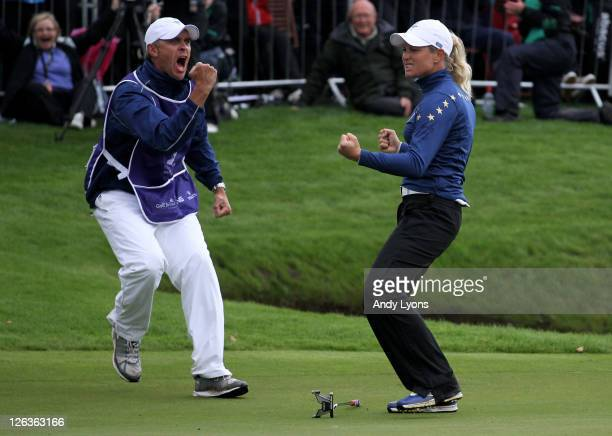Suzann Pettersen of Europe celebrates on the 18th green with caddie Dave Brooker during the singles matches on day three of the 2011 Solheim Cup at...