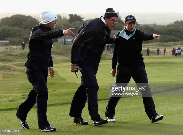 Suzann Pettersen of Norway and Cristie Kerr of the USA indcate to a Rules Official how balls were moving in high winds on the 12th green prior to the...