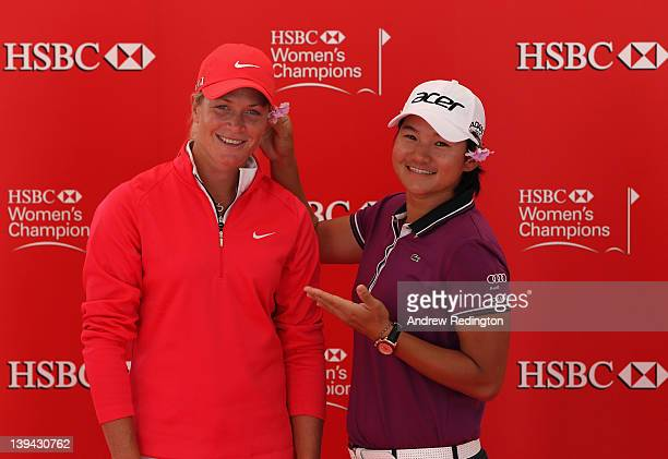 Suzann Pettersen of Norway and Yani Tseng of Taiwan pose as Tseng puts a flower behind Pettersen's ear during a photocall at the Singapore Botanic...