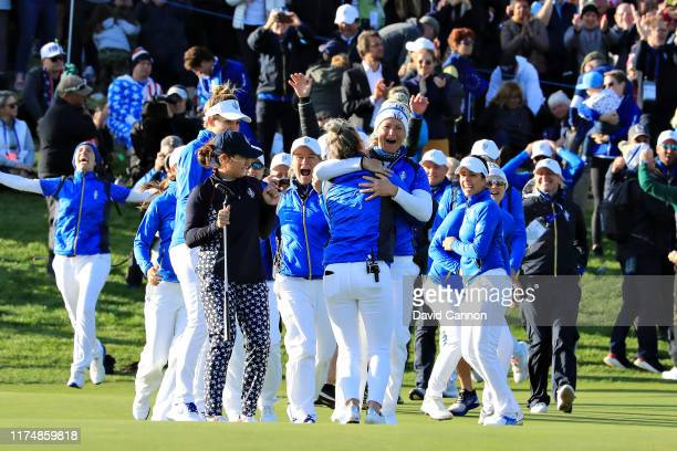 Suzann Pettersen of Team Europe celebrates her winning putt on the eighteenth hole with her team after her match with Marina Alex of Team USA during...