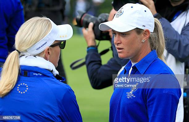 Suzann Pettersen of the European team in deep discussion with her captain Carin Koch about the length of putt that she did not concede to Alison Lee...