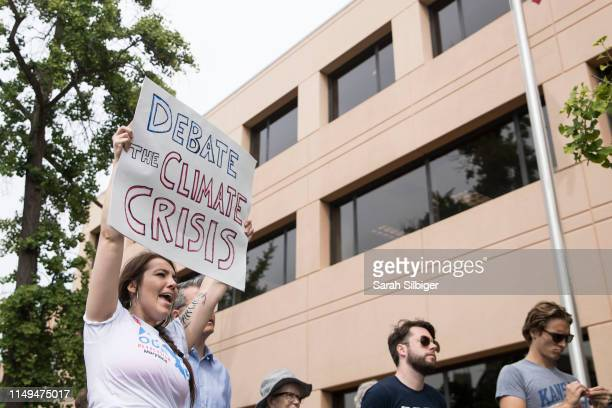 Suzannah Mullen shouts in front of the Democratic National Committee headquarters during a Greenpeace rally to call for a presidential campaign...