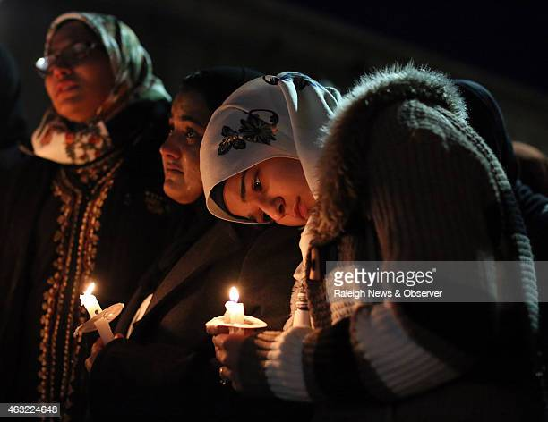 Suzanne Askar rests her head on the shoulder of Safam Mahate a student at North Carolina State University as they stand next to Nida Allam far left...