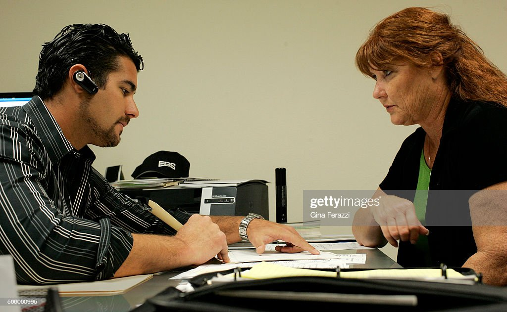 CEO Suzanne DeRossett looks over client contracts with her son, company Vice President John DeRosse : News Photo