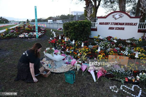 Suzanne Devine Clark visits a memorial setup at Marjory Stoneman Douglas High School for those killed during a mass shooting on February 14, 2019 in...
