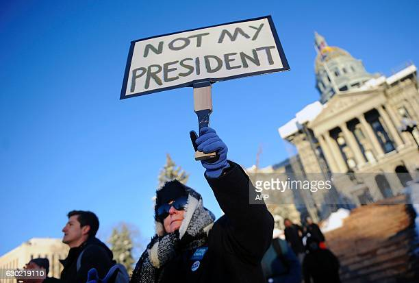 TOPSHOT Suzanne Gould holds a sign during a demonstration against US Presidentelect Donald Trump outside the Colorado Capitol building on the eve of...