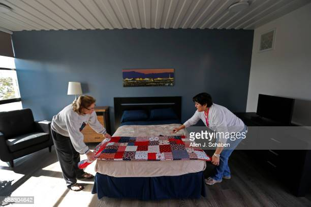 Suzanne Murphy left and Tina Starr American Family Housing executive assistant project manager make a veteran's bed with a handsewn patriotic quilt...
