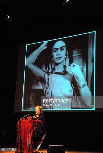 Suzanne von Borsody dahinter auf der Leinwand ein SchwarzWeißFoto als Selbstbildnis von Frida Kahlo mit nacktem Oberkörper Musikalische Lesung 'Frida...