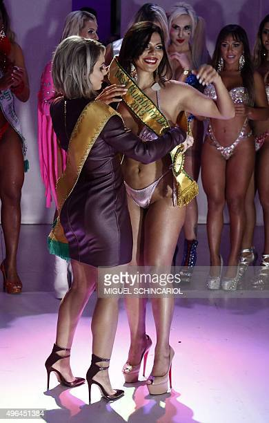 Suzi Cortez from Distrito Federal receives the sash from Indianara Carvalho Miss Bumbum 2014 after winning the Miss Bumbum Brazil 2015 pageant in Sao...