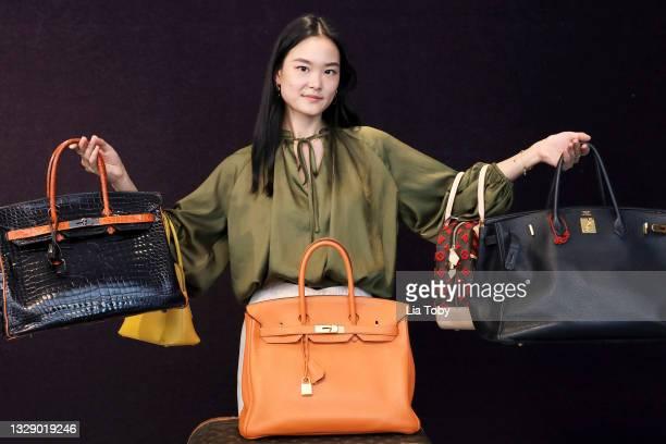 "Suzi Yang, cataloguer for Bonhams displays bags during the ""Bonhams Designer Fashion And Handbags Sale"" photocall at Bonhams on July 16, 2021 in..."