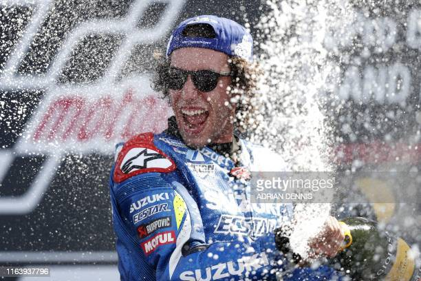 Suzuki Ecstar's Spanish rider Alex Rins sprays champagne on the podium as he celebrates his victory in the Moto GP race of the British Grand Prix at...