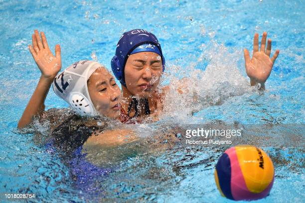 Suzuki Kotori of Japan fights for the ball against Zhang Jing of China during the Women's Water Polo Preliminary Round between Japan and China in the...