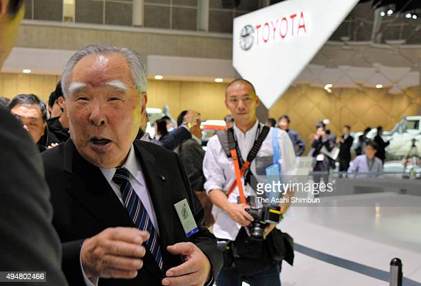 Suzuki Motor Co Chairman Osamu Suzuki questions to a staff at the Toyota Motro Co booth during the Tokyo Motor Show at Tokyo Big Sight on October 29...