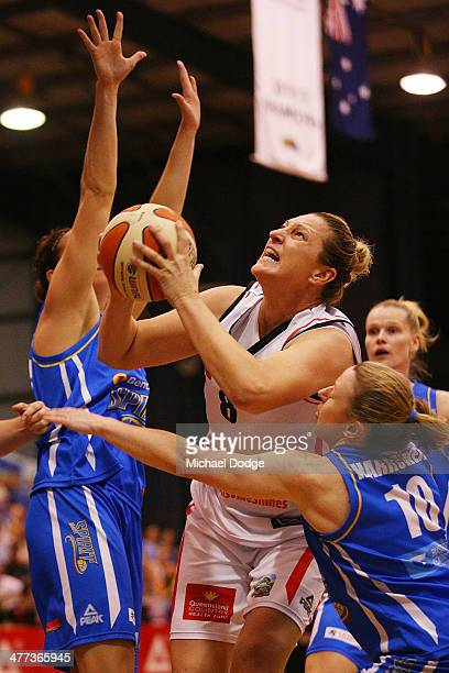 Suzy Batkovic of the Fire drives to the basket against Kelsey Griffin and Kristi Harrower of the Spirit during the WNBL Grand Final match between...